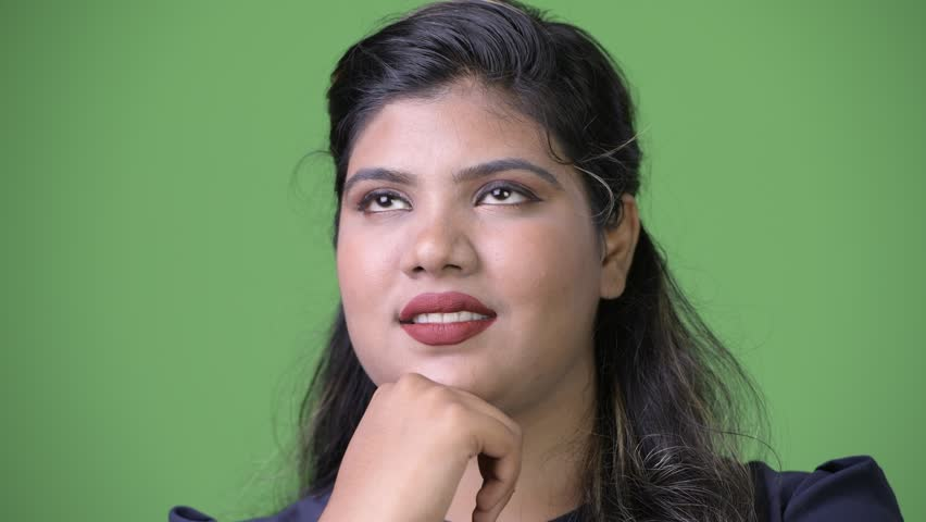 Young overweight beautiful Indian businesswoman against green background | Shutterstock HD Video #1011962585