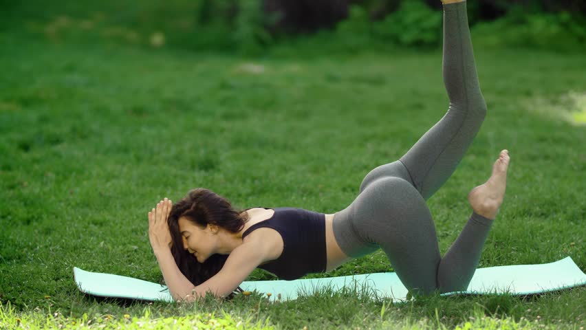 Woman practicing yoga performing yoga-asanas with closed eyes. Young attractive slim girl in bodysuit relaxing and doing exercises, laying on a yoga mat. Gorgeous concentrated mixed race Asian