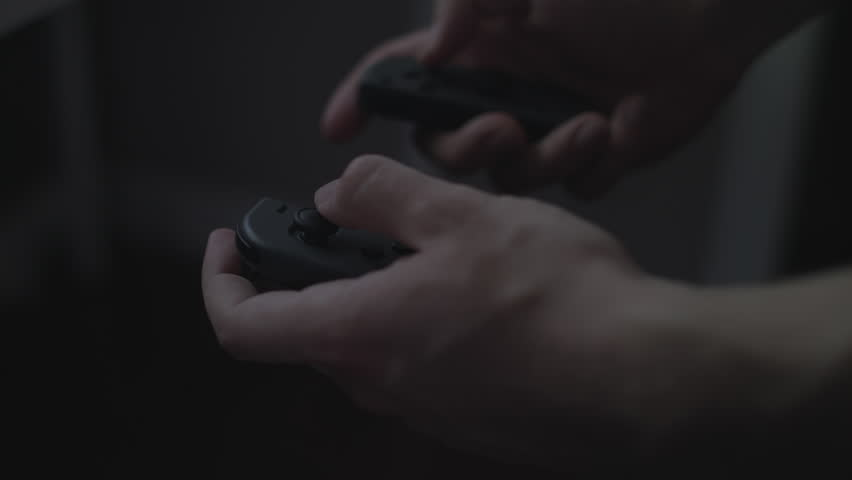 Close up of hands playing with/using dual black video game controllers. #1011963215