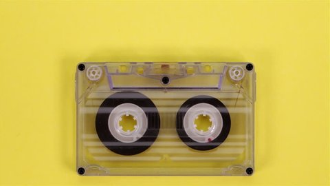Retro music compact cassette reeling tape on yellow background - closeup