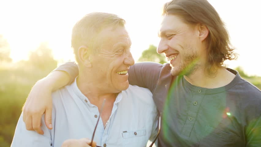 Father and son have a good time on the river bank. Evening sunset. The men talk and laugh. Father takes off his glasses and rubs his eyes. Fathers day | Shutterstock HD Video #1011983975