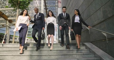 A group of business people of different ethnicities dressed in suits and ties walks proudly after leaving the offices. Concept of: team, success, connection and internationality.
