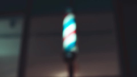 Barber pole spinning at night. International barbershop pole sign. Video with shaking. Soft focus.