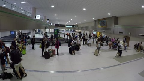 THAILAND AIRPORT 2018: Group of tourists walks towards the airport exit after picking up their suitcases from the moving luggage belt. Cinematic shot of busy baggage claim area in Don Mueang airport.