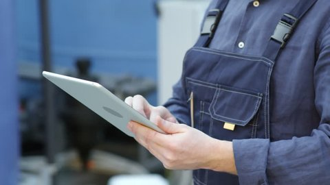 Close up hands of unrecognizable worker in overalls using tablet computer in industrial greenhouse complex