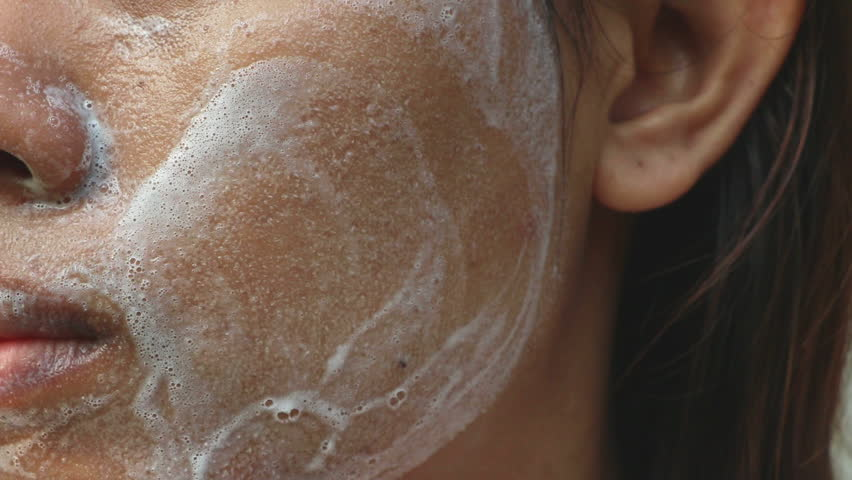 Close up Asia woman cheek. Woman washing face (have wide pores) with white foam by her hand.
