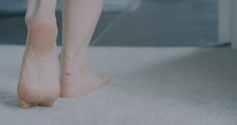Close up on a young woman's feet as she walks from the carpet in her bedroom straight into her ensuite bathroom, she drops her towel and steps into the shower.
