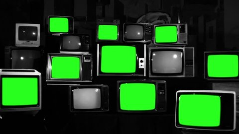 Many Tvs With Green Screens Turning On. Black and White Tone. Zoom Out. Aesthetics of the 80s. Ready to Replace Green Screens with Any Footage or Picture you Want.