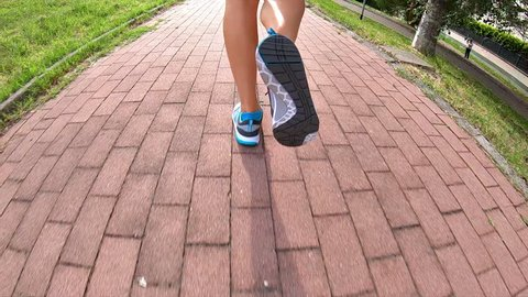 SLOW MOTION running woman legs in gym shoes doing jogging at sunset outdoor. backside view on the park road at dusk.