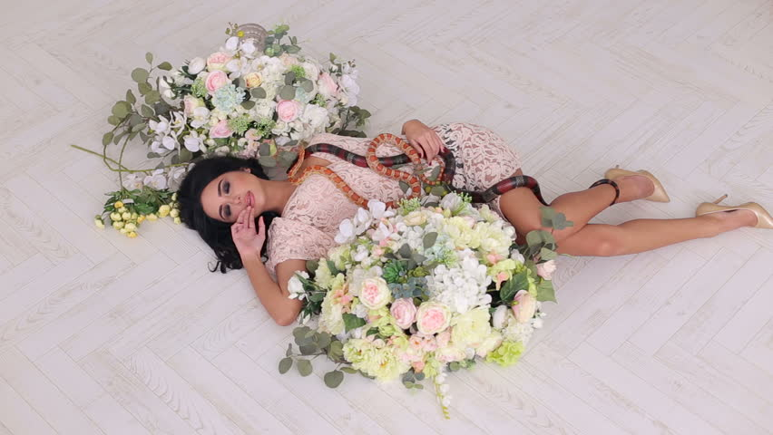 A sexy girl lies on the floor among large bouquets of flowers and two snakes creep along it. Beautiful girl holds a snake in hands on a white background.