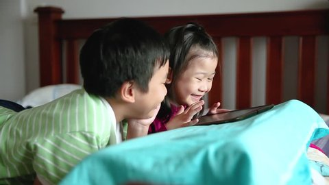 Asian children using digital tablet. Happily brother smiling and cheering his sister near by. Cute girl playing games excitedly on touchpad and lying prone on bed. Focus shifting from boy to girl.