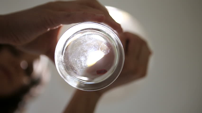 Young woman scattering goji berries in a glass