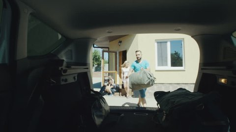View from inside of car of parents with children arranging bags in car trunk and setting off for journey in summertime