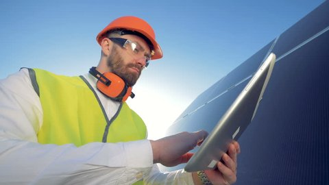 Green energy concept. Engineer is working with his tablet computer and glancing at a solar battery