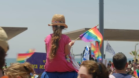 Tel Aviv / Israel 8 June 2018 -  Gay Pride Parade Tel Aviv. Girl sitting on the shoulder of father hanging LGBT flag for rights israeli jews that have fun