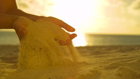 SLOW MOTION, CLOSE UP, LENS FLARE: Unrecognizable female tourist plays with the warm sand at sunset. Picturesque slow motion shot of summer breeze blowing sand out of the young woman's gentle hands.