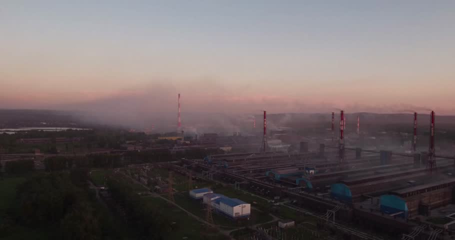 Aerial view of factory plant and landscape in smoke. Air pollution from large industrial plant. 4K
