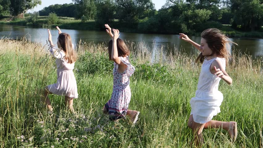 Young girls running on summer countryside near river - teenagers triple sisters twins