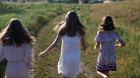 Young girls running on summer countryside meadow road - teenagers triple sisters twins