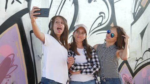 Hang out young teenager triple sisters twins take smartphone selfie on graffiti wall background