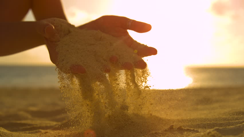 SLOW MOTION, CLOSE UP, LENS FLARE: Unrecognizable female tourist scatters the course sand through her gentle fingertips at beautiful sunset. Cinematic shot of sunrise shining on girl playing with sand