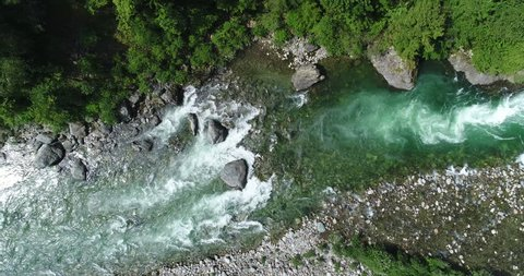 Alpine river seen from above. In summer the river gets thicker due to the thaw of the glaciers. Top view of the river Sesia in Piedmont, Italy.