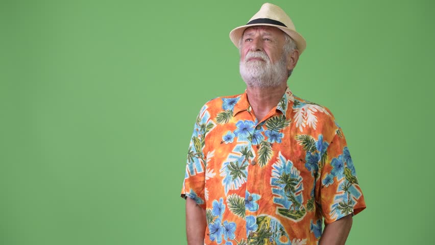 Handsome senior bearded tourist man ready for vacation against green background | Shutterstock HD Video #1012195325