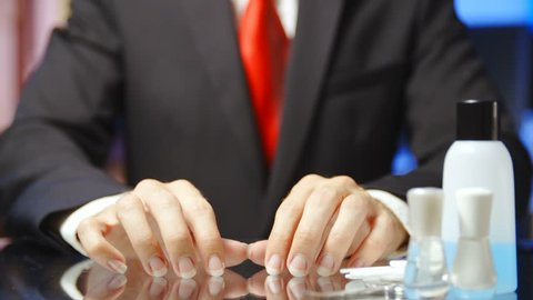 Businessman with long nails tapping on table in slow motion 4K. Static shot of headless male person hands and fingers in focus with long nails. Manicure tools on the right side of the frame.