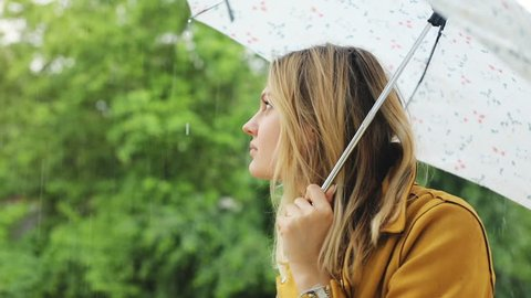 outdoors portrait of attractive calm woman with opened umbrella lonely waiting for the end of the rain in the forest city park day light weather forecast raining season falling raindrops high humidity