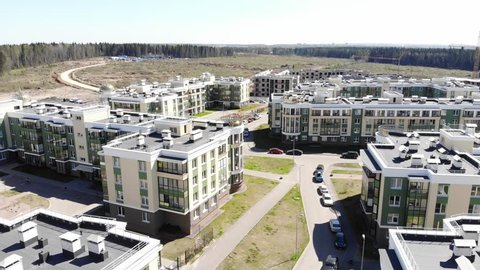 Aerial panorama on rooftops and wasteland. Fly over small town on north surrounded by forest, new modern apartment buildings for families.