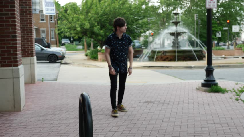 Relaxed young man walking along an urban sidewalk before using a street bollard to leap into the air on passing the camera
