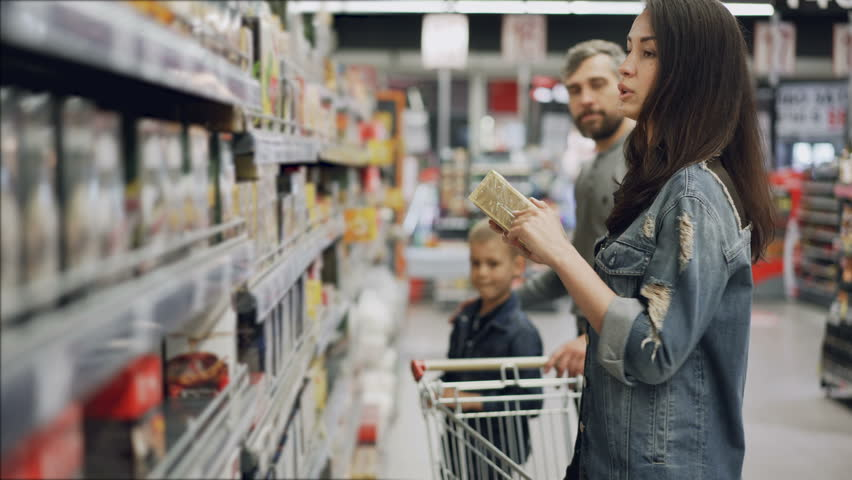 Young woman is choosing tea in food store, her husband and son are helping her looking at products and talking. Buying food and drinks in supermarket concept. | Shutterstock HD Video #1012259885