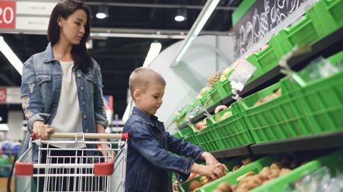 Young family mother and son are buying fruit in grocery store, they are taking pears and kiwifruit and putting them in trolley. Happy customers and supermarket concept.