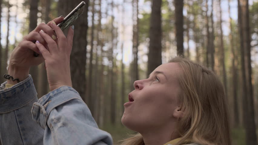The portrait of young pretty woman taking a picture of autumn sunny forest at cellphone holding at hand and looking at screen. Traveling concept of togetherness with nature, outdoor scene
