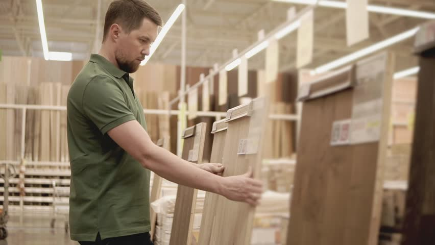 Side view shot of a man looking at and choosing parquet in a building store. Man is taking demonstration sample of parquet and looking it over. | Shutterstock HD Video #1012278275