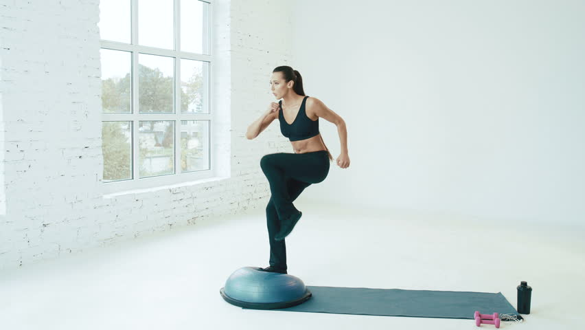 Fit young girl in gym, doing exercises with bosu, aerobics, step-aerobics