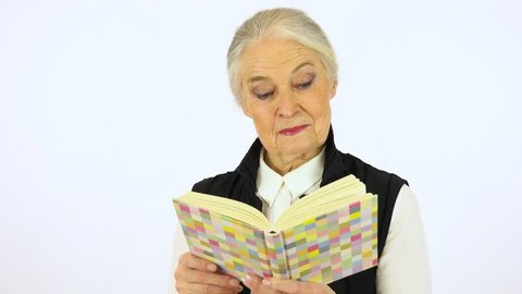 An elderly woman reads a book - white screen studio