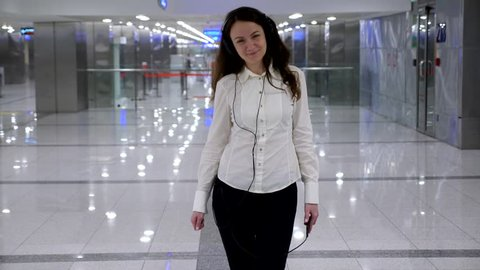 Positive young woman walk at airport listening music on headphones, look to camera, half-length dolly shot. Happy tourist spend time while waiting for connecting flight, recreate oneself with music