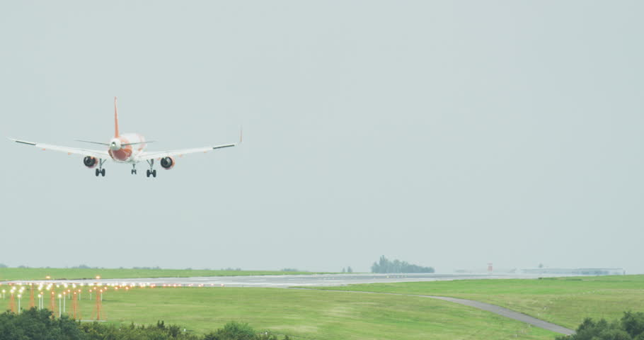 Slow motion daytime close up of a plane landing at Luton airport. Luton airport summer 2017. Ultra HD 4K Ungraded.