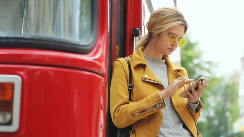 portrait of young sucessful woman using smart phone with red autobus on background in sunny peaceful day checking business plan online conversation clothes designer spring fashion hipster style