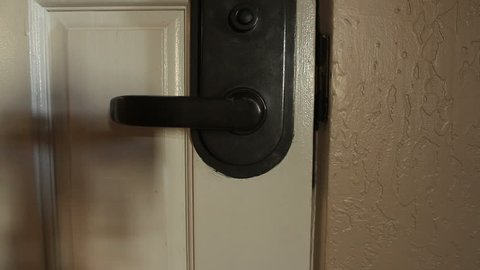 A man hanging a do not disturb sign on a hotel room door