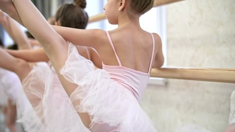 Rear view of group of little girls using ballet barre when doing leg stretching exercises in dance studio, their female teacher controlling them