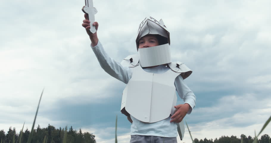 Kid boy wearing cardboard medieval knight armor costume draws a sword from a scabbard against blue sky. 4K UHD 60 FPS SLO MO #1012348685