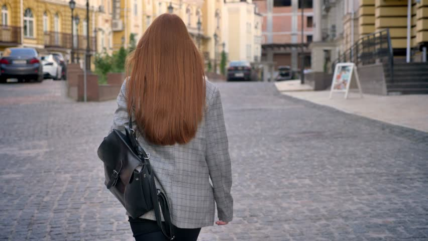 Young woman with long ginger hair walking in the city and looking back, holding backpack, urban street background, back view | Shutterstock HD Video #1012349345