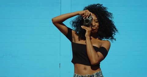 Beautiful young woman shooting photos with film camera against colorful blue wall