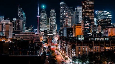 Time lapse of the St Lawrence Market tourist district of downtown Toronto with modern and futuristic financial district office building skyscrapers with car traffic light streaks.