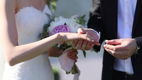 Groom putting wedding ring on brides finger close up summer day no face slow motion festive clothes. Unrecognizable man ringing woman fiance  designer jewellery luxury lifestyle. Bridal fashion
