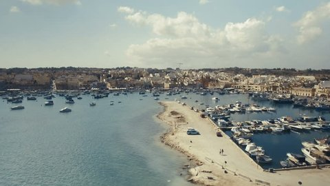 Scenic Aerial shot in Marsaxlokk flying towards a small church