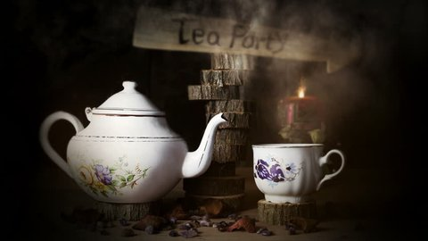 4K Cinemagraph - Cup of Tea and Teapot  On Wooden Table With Arrow Sign, Smoke ,Candle Flame and Light in The Background. Tea Party Concept