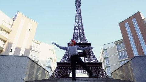 Mime in red beret stripped shirt showing funny scenes at Eiffel Tower background